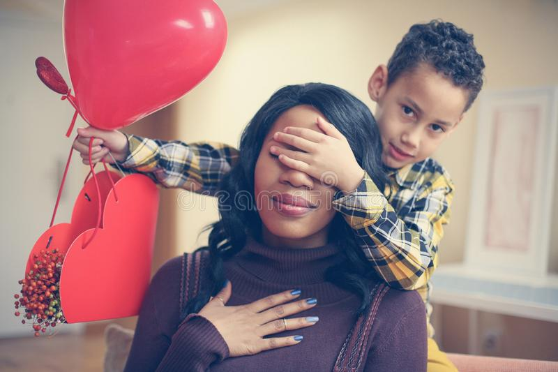 African American boy holding his mother closed eyes. Looking at stock images