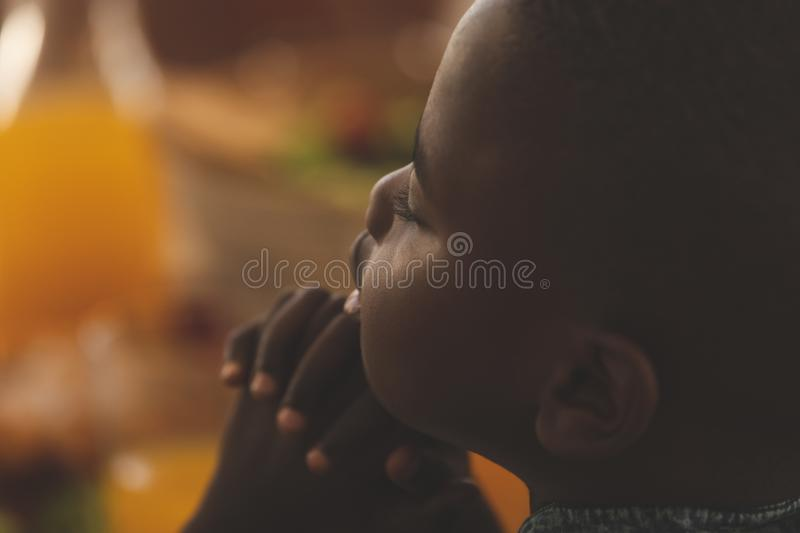 African American boy praying at dining table stock image