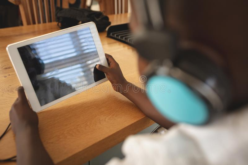 African American boy using digital tablet at dining table in kitchen royalty free stock image