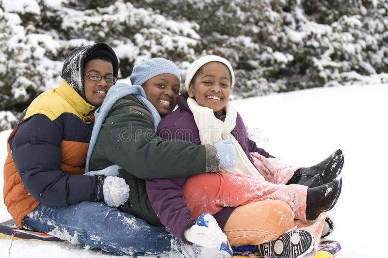 African American brothers and sister sliding on a sled. Brothers and sister sliding on a sled royalty free stock photos