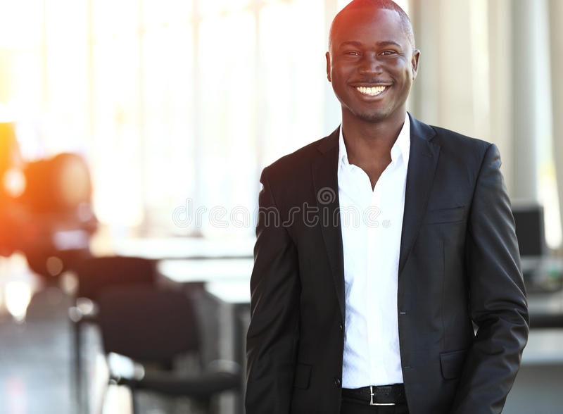 African-American business leader looking at camera in working environment. Image of African-American business leader looking at camera in working environment stock photo
