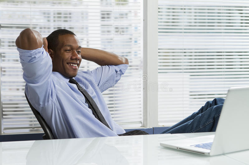 African-American business man taking a break, horizontal. Young black business man taking a break at his desk and looking at computer royalty free stock photo