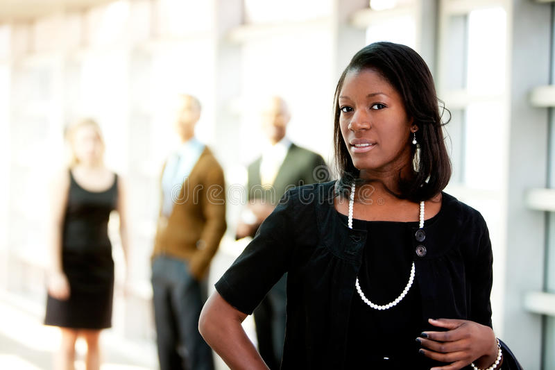African American Business Woman. An african american business woman with colleagues in the background royalty free stock photography