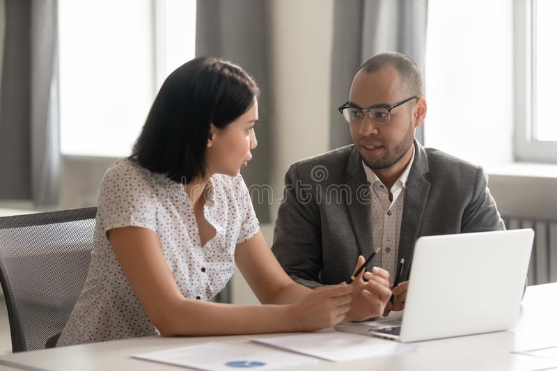 African American businessman and Asian businesswoman discussing project royalty free stock image