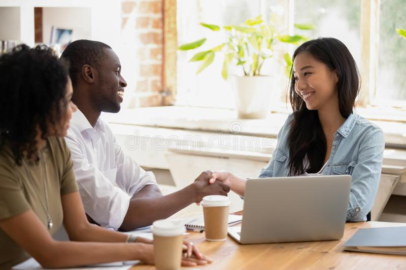 African businessman handshaking asian businesswoman thanking for good work stock images
