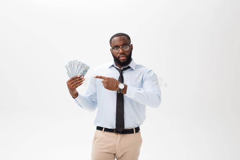 African American businessman holding Cash and serious looking at camera. Indoor, isolated on gray background. royalty free stock photos