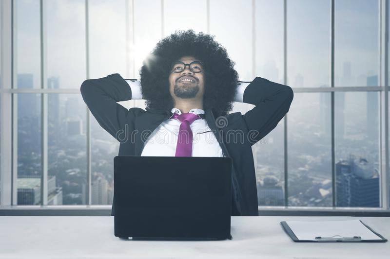 African american with laptop relaxing at office stock photos