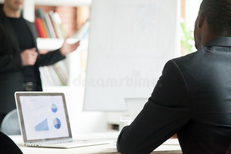 African american businessman listening to presentation, rear clo royalty free stock image