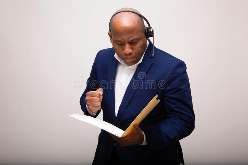 African American Businessman Looks Through File stock photography