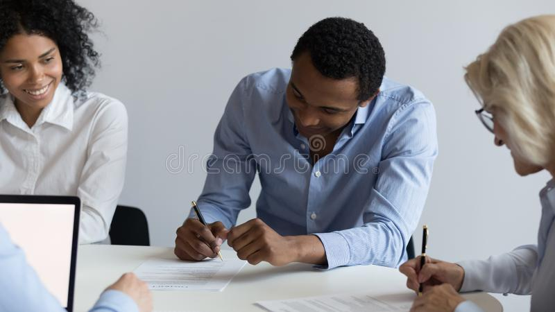 African American businessman and mature businesswoman signing contract. African American businessman and mature businesswoman signing paper document, contract at stock photography