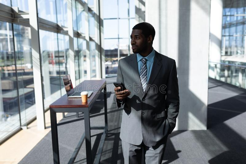 African-American businessman with mobile phone looking away in office stock photography