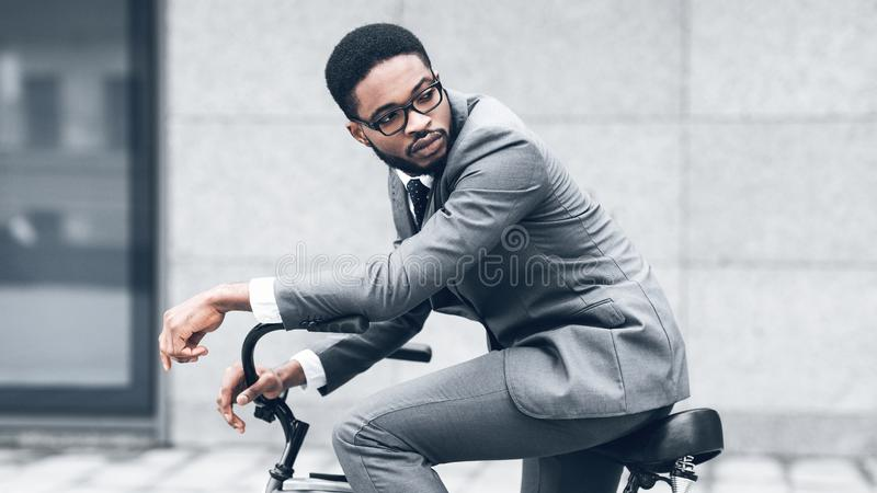 African-american businessman riding bicycle to work in morning. Looking back against office building royalty free stock images