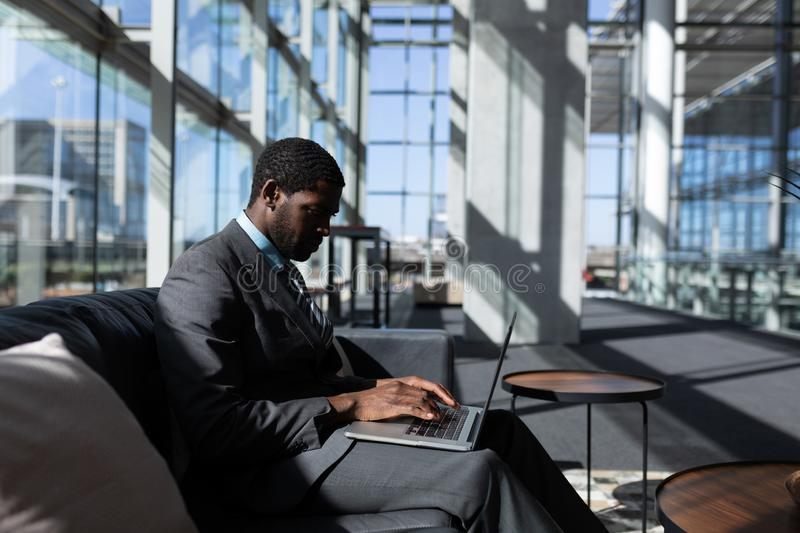African-American businessman sitting on the sofa and using laptop in modern office stock photo