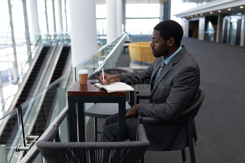 African-American businessman sitting at table and writing on diary in office royalty free stock image