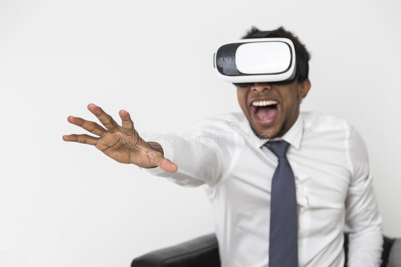 African American businessman in vr glasses. Portrait of an African American man in a white shirt who is sitting in a leather armchair and wearing vr glasses stock image