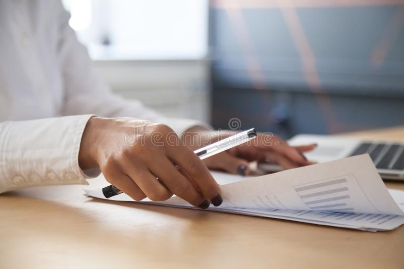 African-american businesswoman analyzing statistics report worki. African american businesswoman analyzing project statistics result in report working with stock image