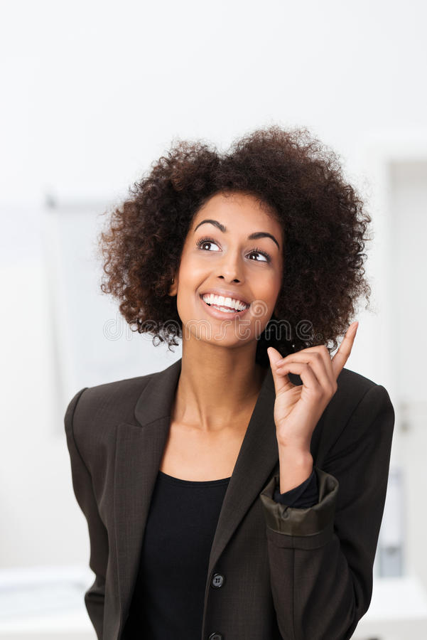 African American businesswoman with a bright idea. Smiling with glee and raising her finger royalty free stock photo