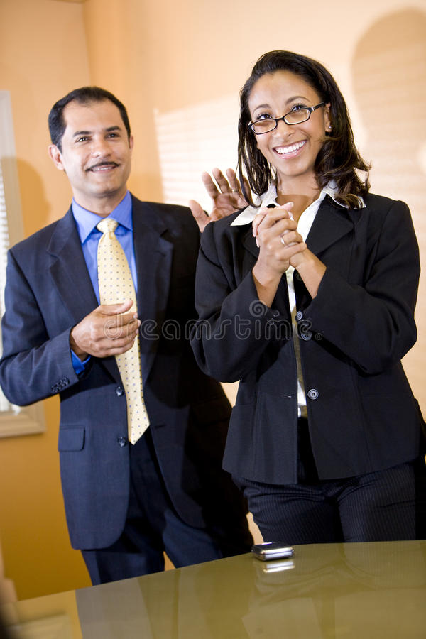 African-American businesswoman getting pat on back. Successful young African-American female office worker getting pat on back from middle-aged Hispanic male royalty free stock photography