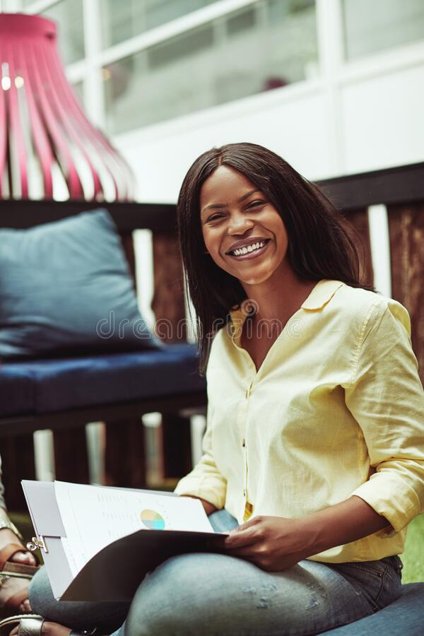 African American businesswoman smiling during a casual office me stock photography