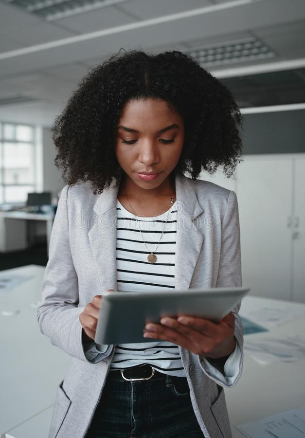 An attractive african american businesswoman standing in front of desk using a digital tablet in modern office royalty free stock photo