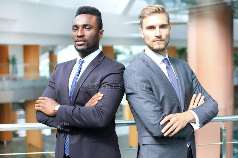 African american and caucasian business partners standing back to back together and looking in camera, in office. stock image