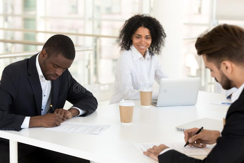 African american and caucasian businessmen signing contracts con stock photos