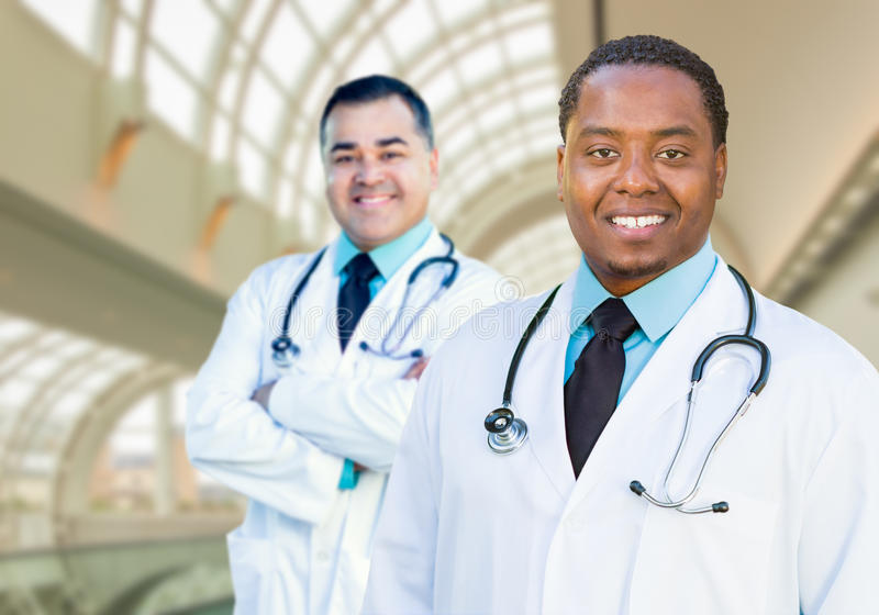 African American and Caucasian Male Doctors Inside Hospital. Office royalty free stock photography