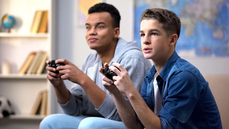 African-american and caucasian teenagers playing video games, gaming addiction. Stock photo royalty free stock photo