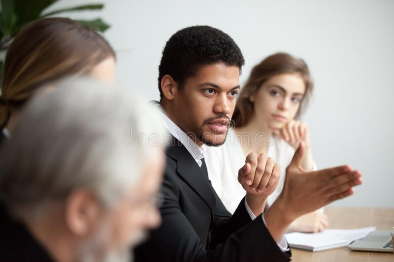 African american ceo talking giving instructions at diverse team. Serious african american ceo giving instructions at diverse team meeting, confident black stock images