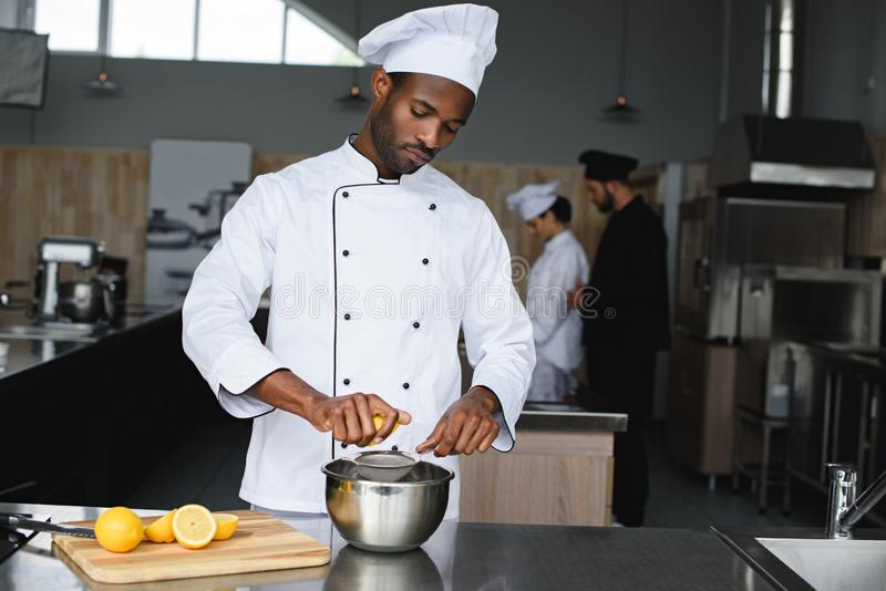 african american chef squeezing lemons stock photography