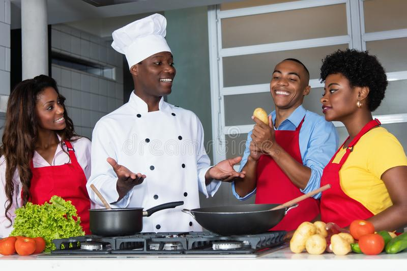 African american chef teaching women and men at kitchen stock image