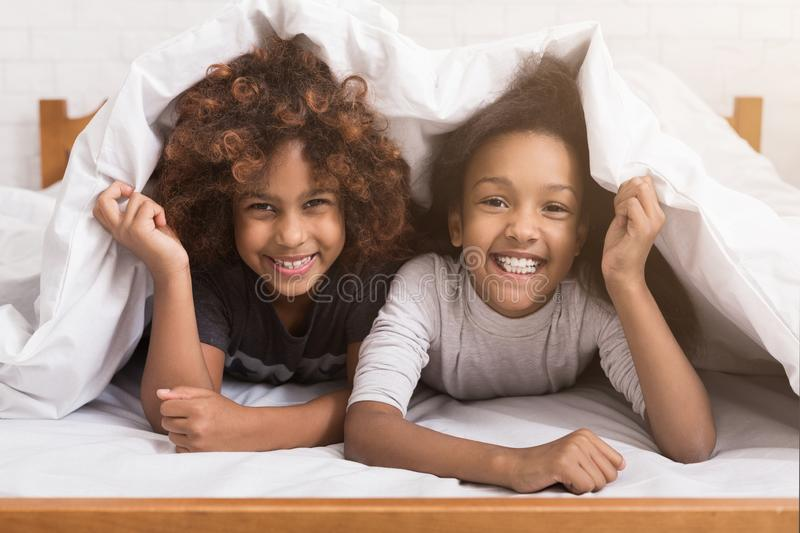 African-american child girls lying under blanket on bed royalty free stock photos