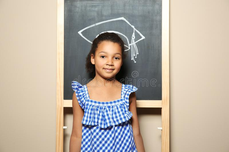 African-American child standing at blackboard with chalk drawn academic cap. Education stock photography