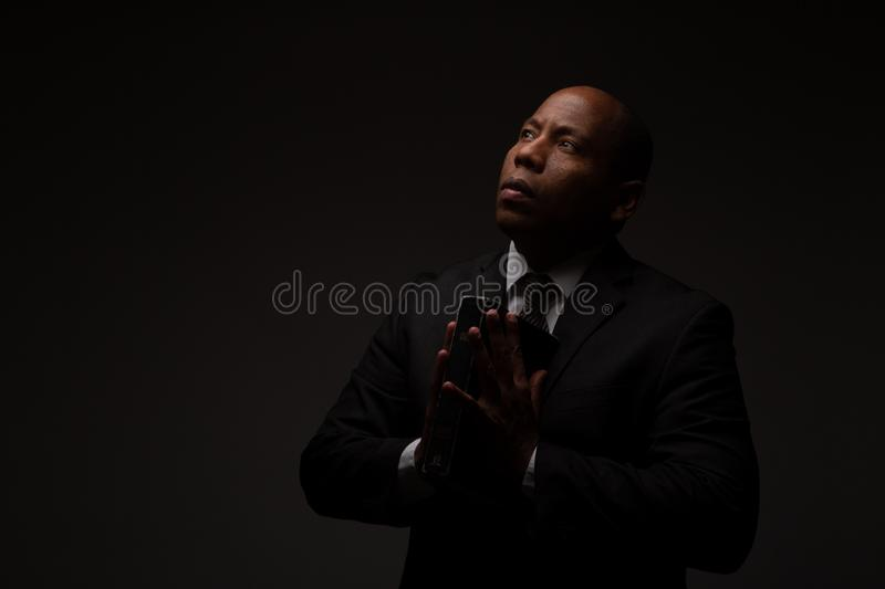 African American Christian Man Holding the Word of God, the Bible, The Scriptures, and Deeply Meditating. In Dark Background royalty free stock photos