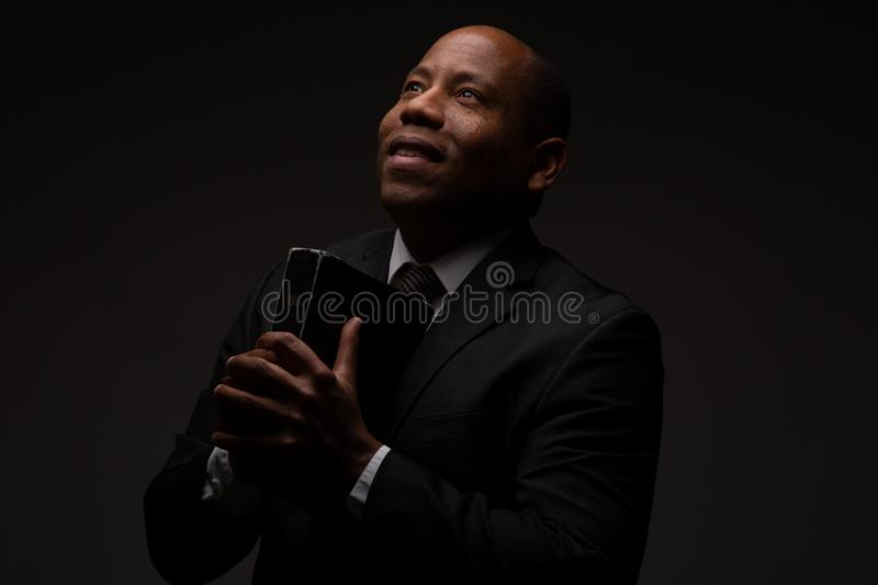 African American Christian Man Reading the Holy Scriptures, the Bible, The Word of God. On Dark Background royalty free stock photos