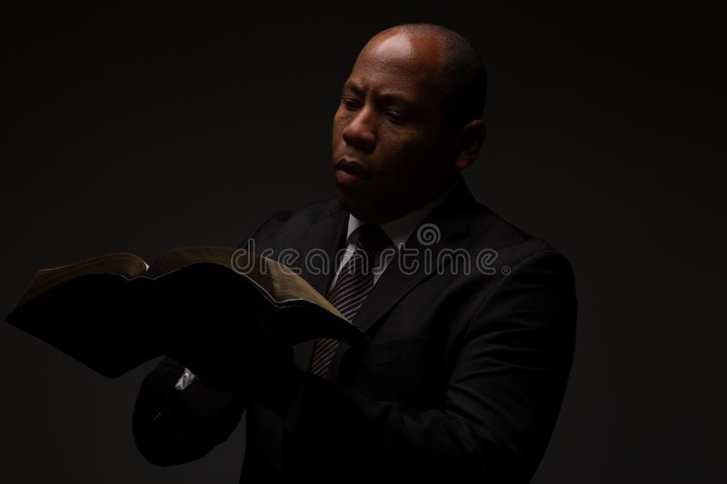 African American Christian Man Reading the Holy Scriptures, the Bible, The Word of God. On Dark Background stock image