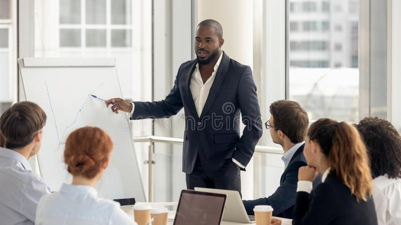 African american coach talking to audience giving presentation on flipchart. African american conference speaker coach talk to audience give presentation on stock photos