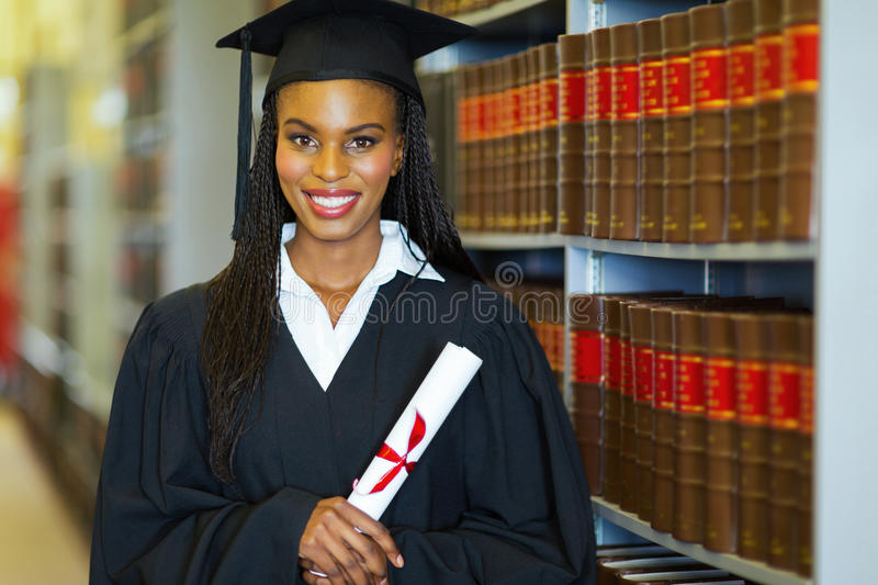 African american college graduate. Pretty african american college student wearing graduation attire in library royalty free stock photography
