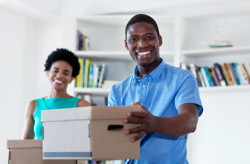 African american couple with boxes at new home stock image
