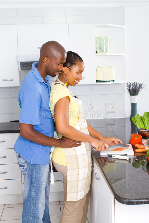 African american couple cooking. Happy african american couple cooking in kitchen royalty free stock photo