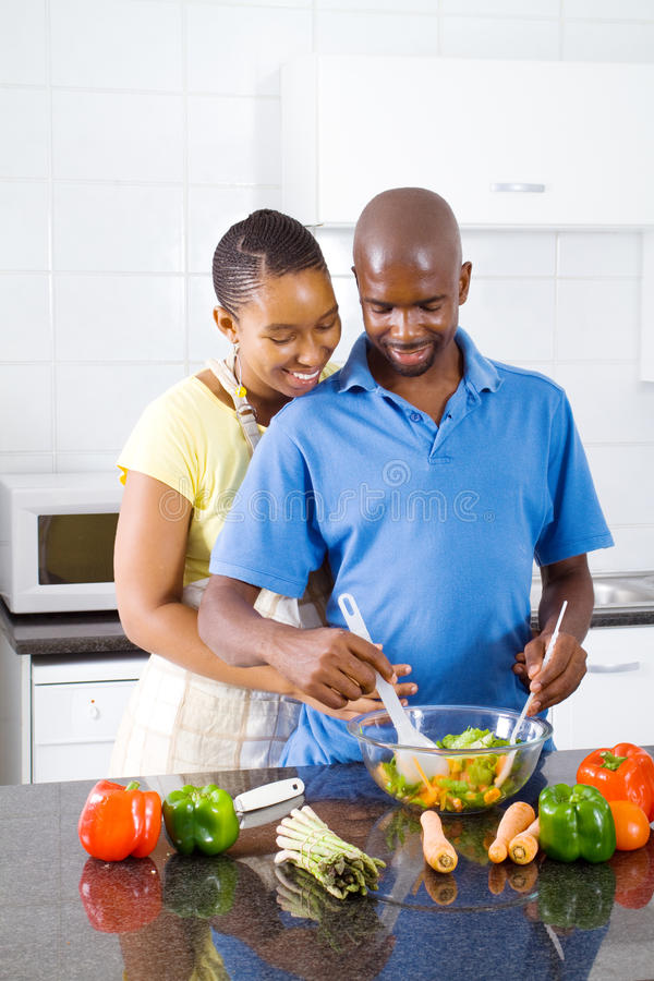 African american couple cooking. Young african american couple cooking in kitchen stock photos