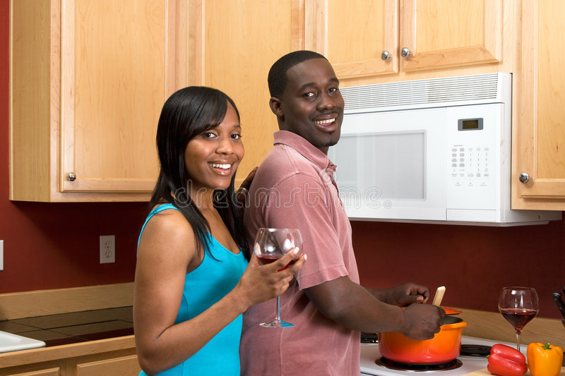 African American Couple Cooking - Horizontal. Attractive young African American couple cooking dinner together and drinking red wine. Horizontally framed shot royalty free stock image