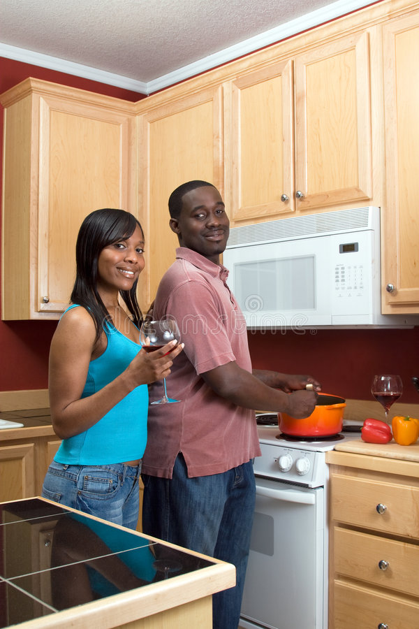 African American Couple Cooking - Vertical. Attractive smiling young African American couple cooking dinner together and drinking red wine. Vertically framed royalty free stock images