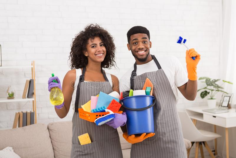 African-american couple holding cleaning tools and detergents royalty free stock photos