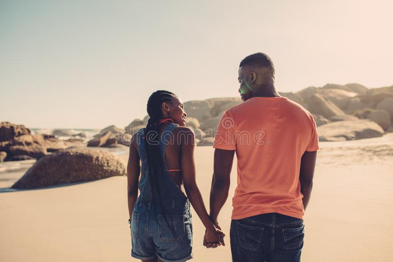 Man and woman in love strolling on the beach. African american couple holding hands and walking along the beach. Man and women in love strolling on the seashore stock photo