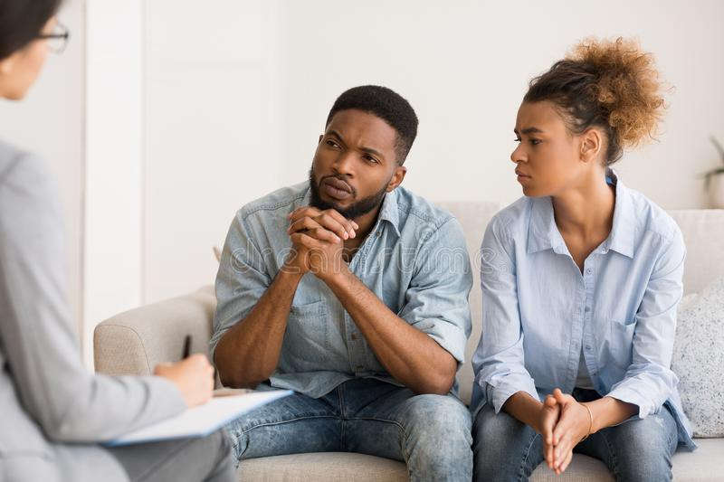 African American Couple Listening To Psychologist`s Advice On Therapy Session. Marital Therapy. Black Couple Listening To Counselor`s Advice Sitting On Couch In royalty free stock image