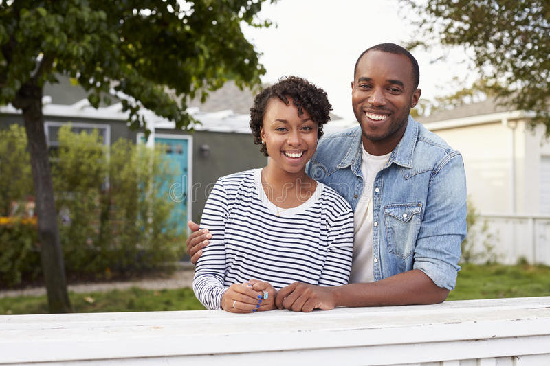 African American couple look to camera outside their house stock image