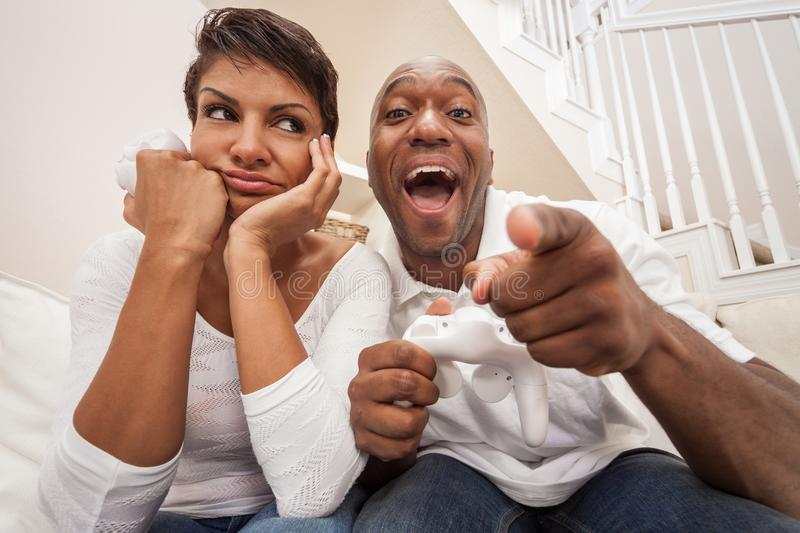African American Couple Having Fun Playing Video Console Game. African American couple, men and woman, having fun playing video console games together. The men royalty free stock photography