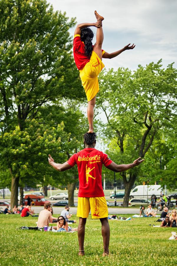 African American couple performing acrobatics show in front of the audiance in Mount Royal Park stock photo