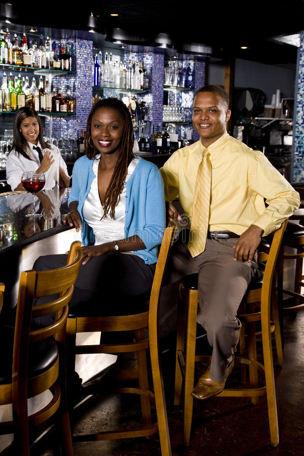 African American couple sitting at a bar royalty free stock photography